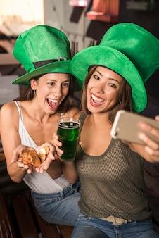 Rozochocone młode kobiety z szkłem napój i złote monety bierze selfie na smartphone