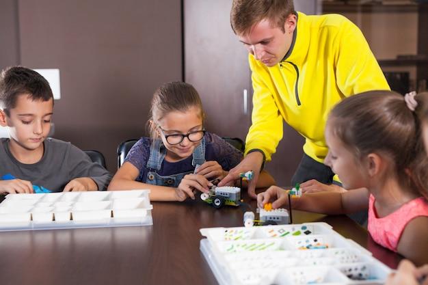 Rozochocone uśmiechnięte dzieci budują konstruktora.