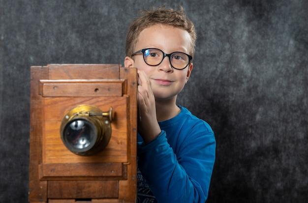 Rozochoconej chłopiec retro fotograf z rocznik drewnianą kamerą