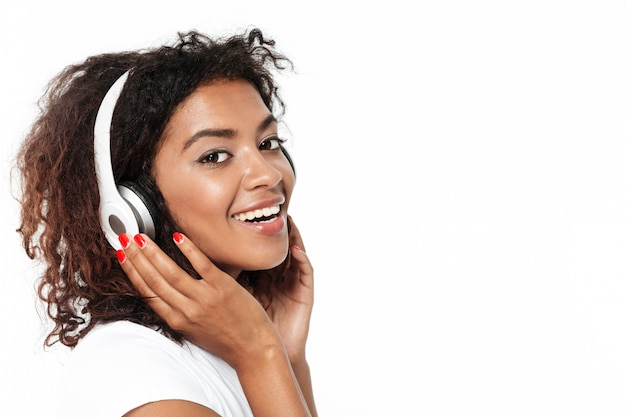 Rozochoconej młodej afrykańskiej damy słuchająca muzyka w hełmofonach.