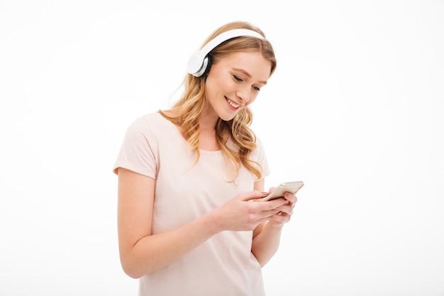 Rozochoconej młodej damy słuchająca muzyka używać telefon komórkowego.