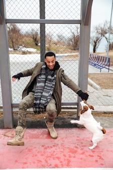 Rozochocony afrykański mężczyzna bawić się z psem i śmia się outdoors