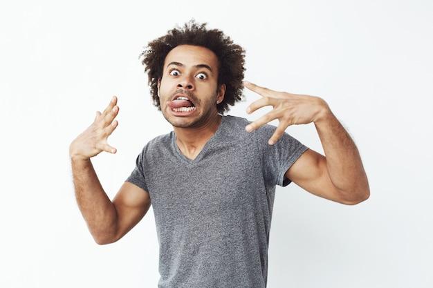 Rozochocony afrykański mężczyzna robi śmiesznej twarzy oszukiwać.