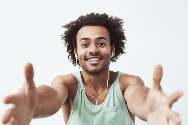 Rozochocony afrykański mężczyzna uśmiecha się rozciąganie ręki w przewodowych hełmofonach próbuje kraść twój telefon komórkowego.