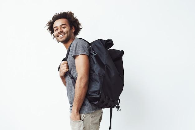 Rozochocony afrykański mężczyzna z plecaka ono uśmiecha się.