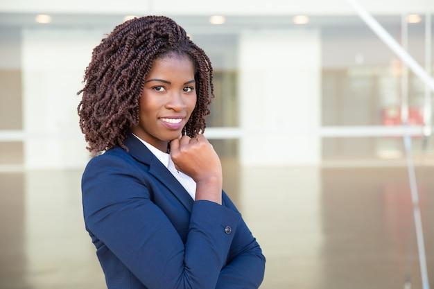 Rozochocony amerykanina afrykańskiego pochodzenia bizneswoman ono uśmiecha się przy kamerą