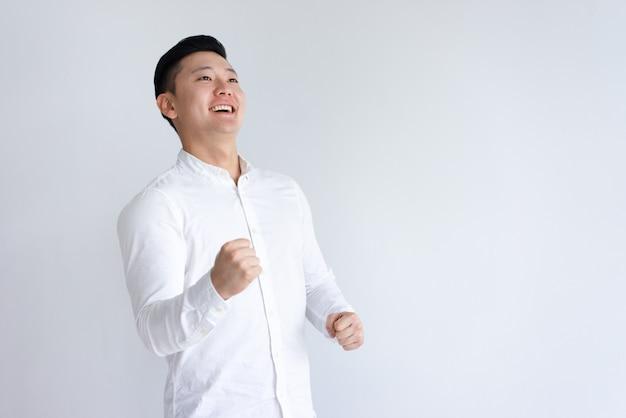 Rozochocony azjatycki mężczyzna pompuje pięści i patrzeje daleko od