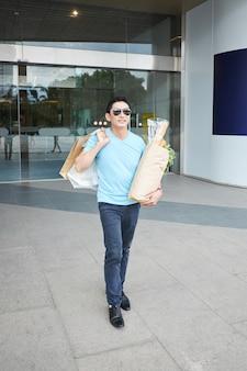 Rozochocony azjatycki mężczyzna pozuje z torba na zakupy i sklepami spożywczymi przy budynku wejściem