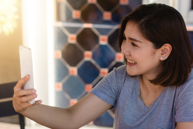 Rozochocony azjatykci młodej kobiety obsiadanie w cukiernianym używa smartphone dla opowiadać, czytać i texting