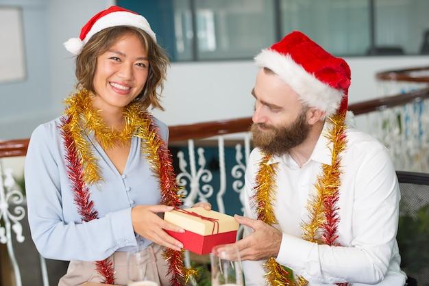 Rozochocony biurowy asystent w santa kapeluszu daje bożenarodzeniowemu prezentowi