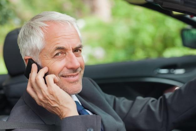 Rozochocony biznesmen jedzie drogiego kabriolet na telefonie