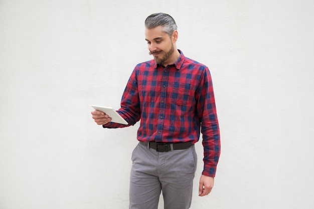 Rozochocony brodaty mężczyzna używa pastylka komputer osobistego