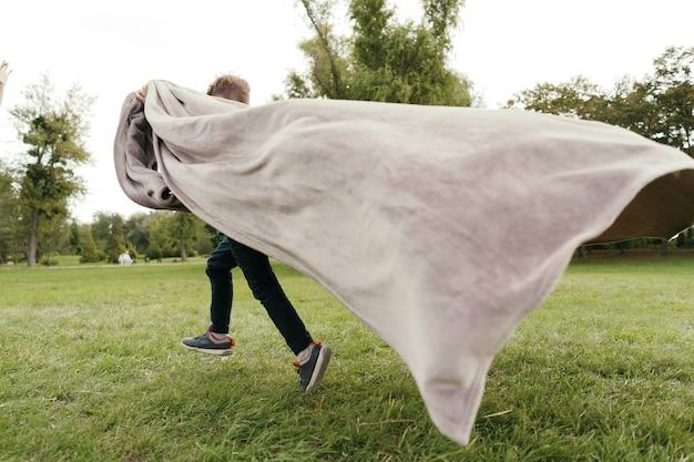 Rozochocony chłopiec bieg z latającym koc w parku