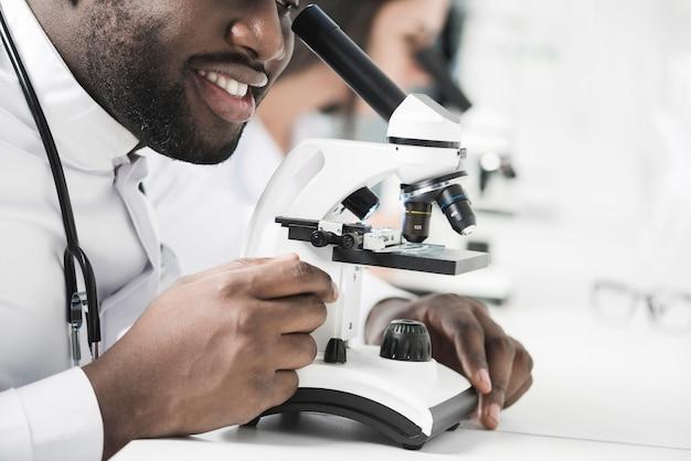 Rozochocony czarny student medycyny używa mikroskop