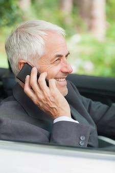 Rozochocony dojrzały biznesmen jedzie drogowego kabriolet na telefonie