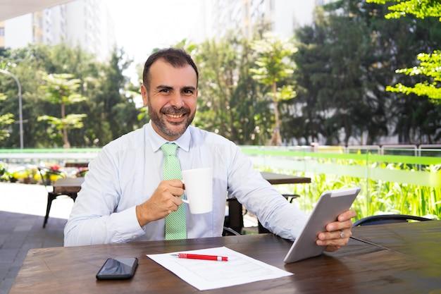 Rozochocony dojrzały biznesmen pije kawę i używa komputer osobisty pastylkę