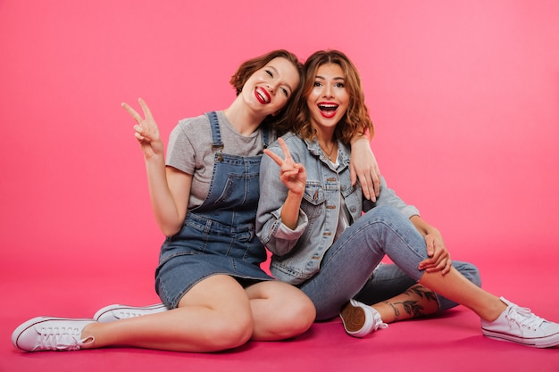 Rozochocony dwa kobiet przyjaciele siedzi na podłoga