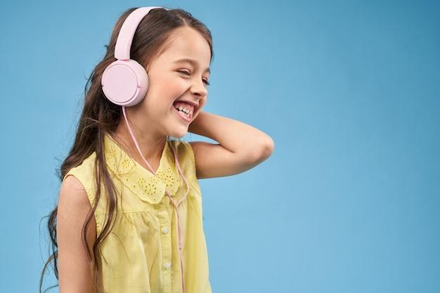 Rozochocony dziecko ono uśmiecha się i pozuje w różowych hełmofonach.