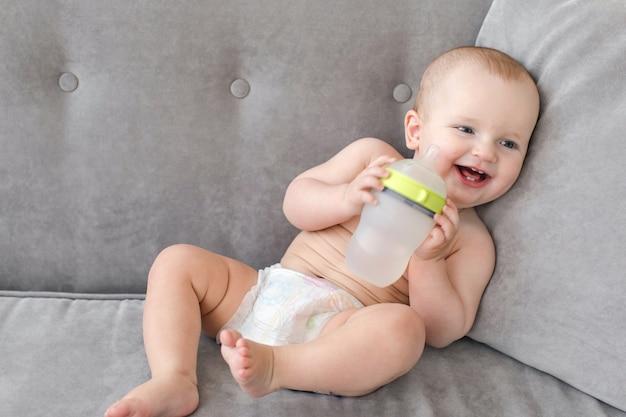 Rozochocony dziecko z butelką na kanapie