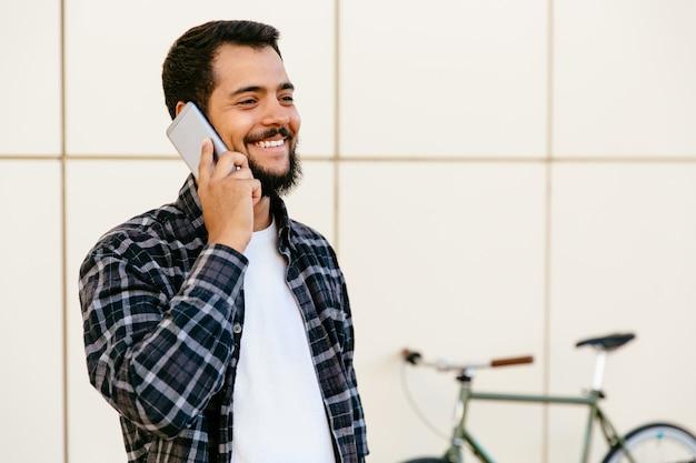 Rozochocony elegancki młody brodaty mężczyzna komunikuje telefonem komórkowym