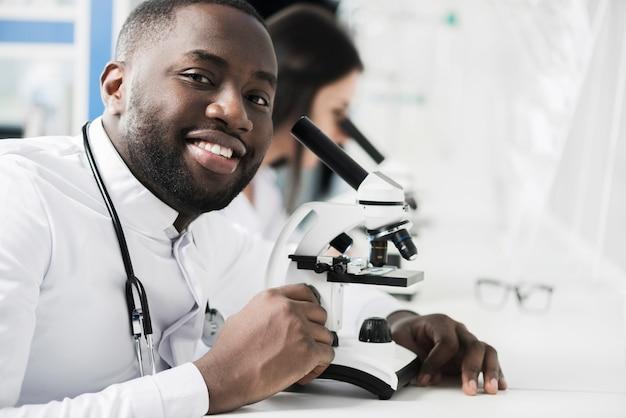 Rozochocony etniczny student medycyny przy mikroskopem