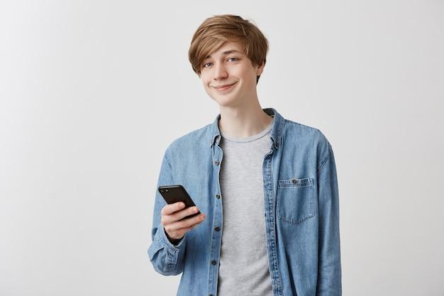 Rozochocony jasnowłosy caucasian męski uczeń w danim koszula przegląda internet na smartphone, odpoczywa po zajęć, patrzeje ekran i ono uśmiecha się. nowoczesne technologie i komunikacja