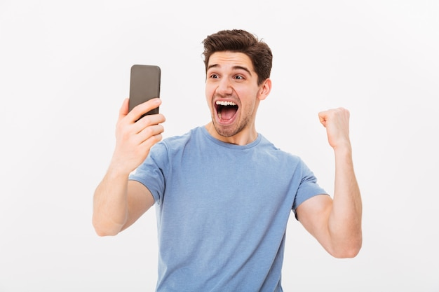Rozochocony krzyczący mężczyzna trzyma koszulkę w koszulce i cieszy się z zamkniętymi oczami nad szarości ścianą