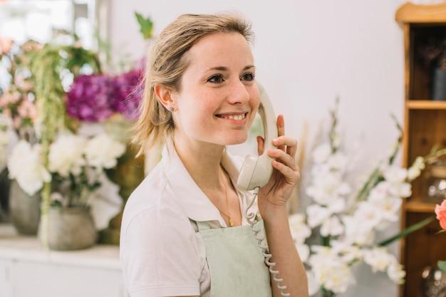 Rozochocony kwiaciarni mówienie na telefonie