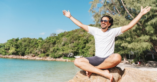 Rozochocony łaciński młody człowiek w białych koszulkach i okularach przeciwsłonecznych z rękami rozprzestrzeniającymi otwierał obsiadanie przy tropikalną plażą, szczęściem, wolnością wakacje i podróży pojęciem.