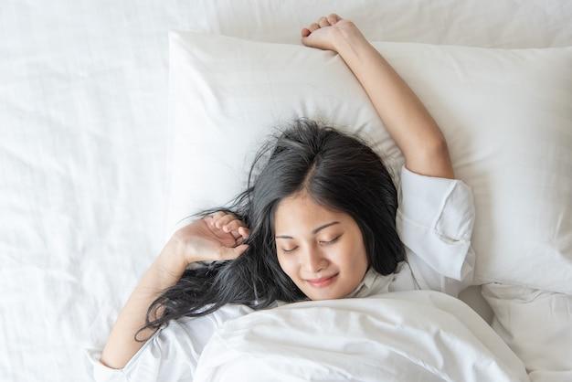 Rozochocony ładny azjatykci kobieta uśmiech i szczęśliwy na łóżku w sypialni