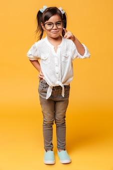 Rozochocony małej dziewczynki dziecko jest ubranym szkła wskazuje ty.