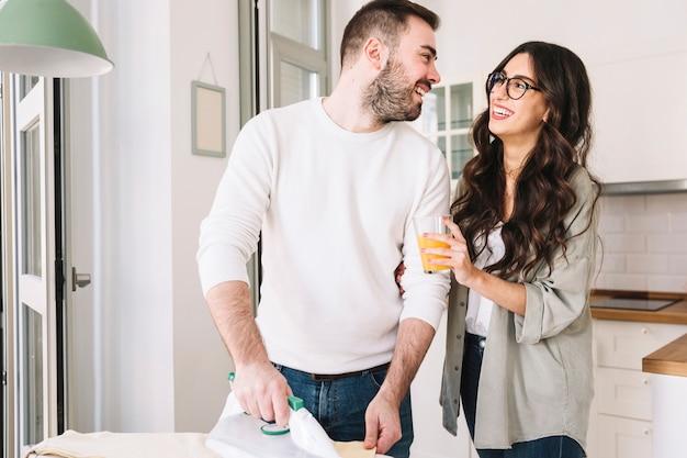 Rozochocony mężczyzna i kobieta odprasowywa w domu