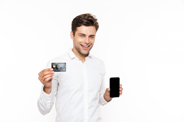 Rozochocony mężczyzna ono uśmiecha się z ciemnym włosy podczas gdy trzymający smartphone i kredytową kartę