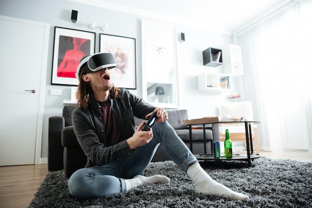 Rozochocony mężczyzna siedzi w domu bawić się gry