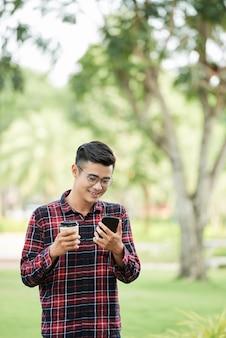 Rozochocony mężczyzna z kawą i telefonem