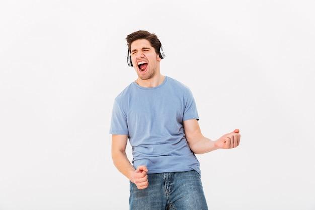 Rozochocony mężczyzna z krótkimi ciemnymi włosami słucha muzyka przez słuchawek i postępuje jak gitarzysta, odizolowywający nad biel ścianą