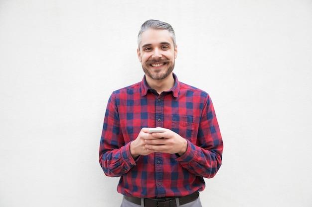 Rozochocony mężczyzna z smartphone ono uśmiecha się