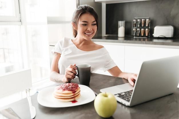 Rozochocony młodej kobiety obsiadanie przy kuchennym używa laptopem