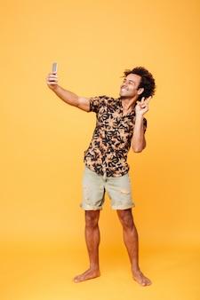 Rozochocony młody afrykański mężczyzna robi selfie z pokoju gestem