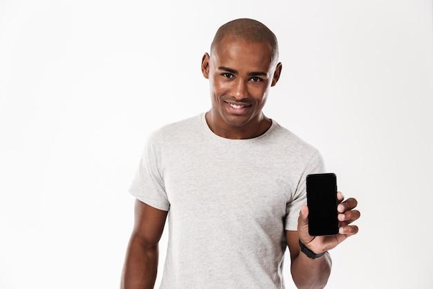 Rozochocony młody afrykański mężczyzna seansu pokaz telefon komórkowy.