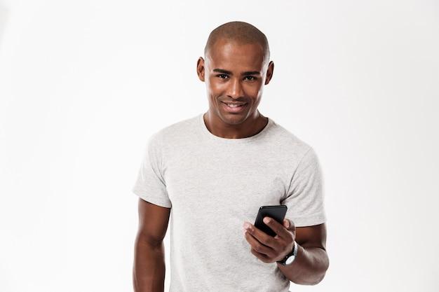Rozochocony młody afrykański mężczyzna używa telefon komórkowego.