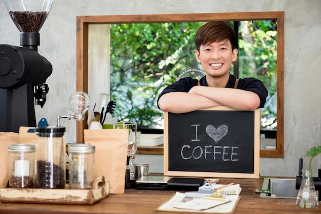Rozochocony młody azjatycki mężczyzna przedsiębiorca przy kontuarem w sklep z kawą