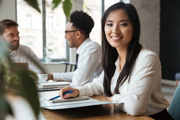 Rozochocony młody azjatykci bizneswoman blisko kolegów.