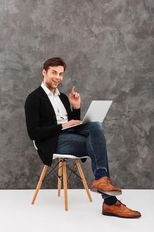 Rozochocony młody biznesmen używa laptop pomysł.