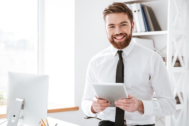 Rozochocony młody biznesmena mienia pastylki komputer w rękach.