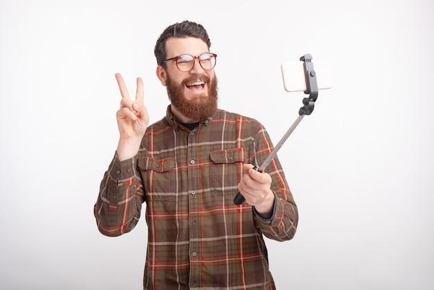 Rozochocony młody brodaty mężczyzna robi fotografii z selfie kijem n bielu przestrzenią.