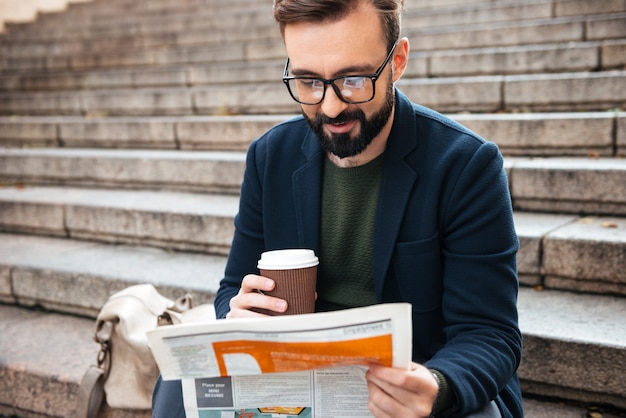 Rozochocony młody brodaty mężczyzna siedzi outdoors na krokach czyta gazetę