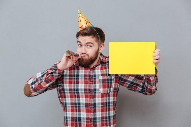 Rozochocony młody brodaty urodzinowy mężczyzna trzyma puste miejsce deskę