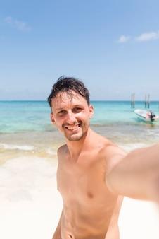Rozochocony młody człowiek bierze selfie przy plażą