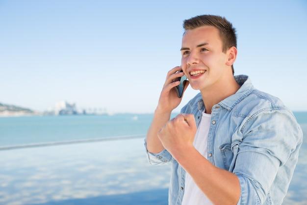 Rozochocony młody człowiek opowiada na telefonie i pokazuje wygranego gest